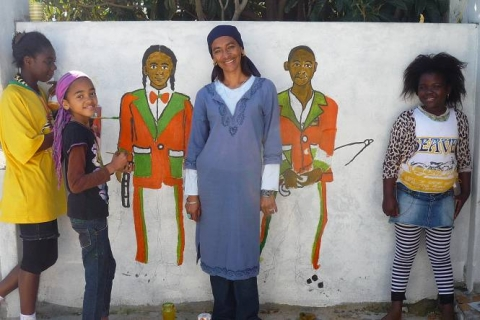 Figure 21: Mrs. Collins, her daughter and other children while joining in painting a copy of the photograph of her two children in the D6 Minstrels Carnival onto her wall