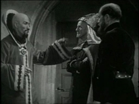 A sophisticated composition. As the priest leaves by the back door, the camera pans to the right to frame Ming and Zarkov as equals, at a time when the scientist's role is still ambiguous for the viewer.
