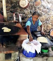 Sra Maximina Guerrero echando tortillas en estufa ahorradora de leña